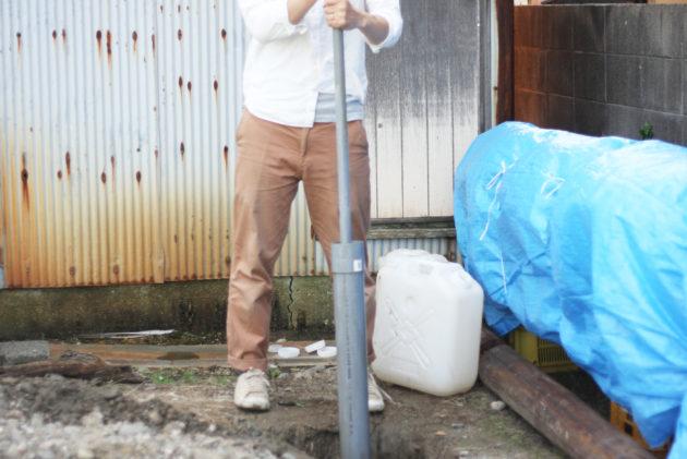 塩ビパイプを上下に動かし、穴を掘る作業